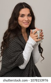 Female brunette in fashion gray cardigan holding big cup of coffee. Mid age woman over 35 years old beauty concept.