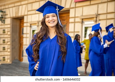 Female brunette latino college or high school graduate smiling confidently wearing  blue cap and gown at graduation