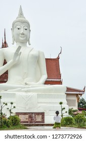 A female buddhist is paying respect and maditate toward a big white buddha image in Thailand. Peaceful and Mercy White Big Buddha Image in Thailand.
