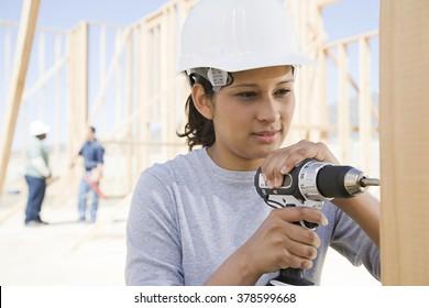 A female builder drilling