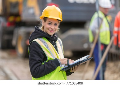 female builder in hardhat with tablet pac at construction with her team