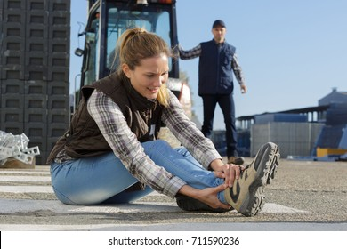 female builder putting working shoes on