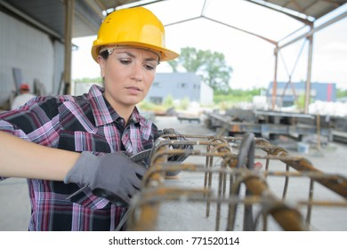 female builder with stock rebar at construction