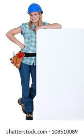 Female builder stood with advertising panel