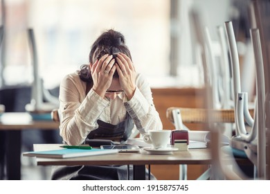 Female busines owner holds her head in hands in desperation over paperwork and tax declaration in a closed pub.