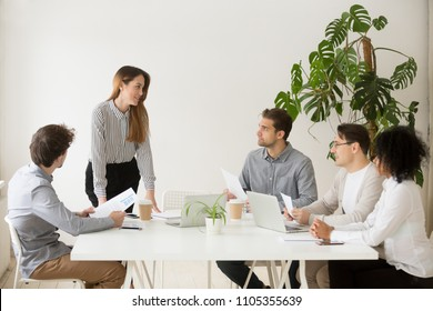 Female business coach making presentation to office workers at meeting, giving handouts to employees, team leader presenting company financial statistics to colleagues. Concept of leadership