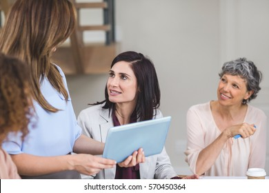 Female business colleagues discussing on digital tablet in office