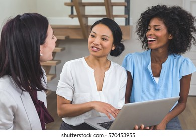 Female business colleagues discussing on laptop in office