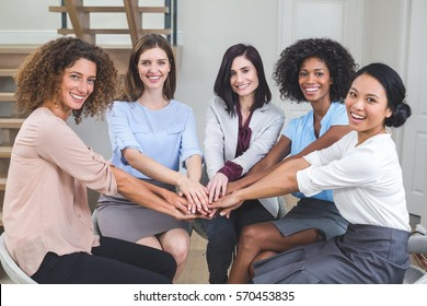 Female business colleagues putting their hands together in office