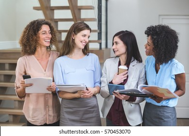 Female business colleagues standing together with file and digital tablet in office