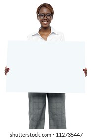 Female business executive holding blank billboard and showing it to camera