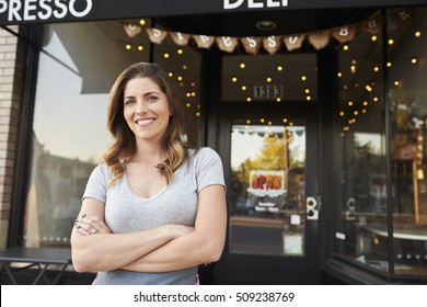 Female business owner stands outside cafe with arms crossed