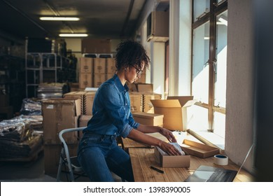 Female business owner working, packing the order for shipping to customer. Female entrepreneur packaging box for delivery.