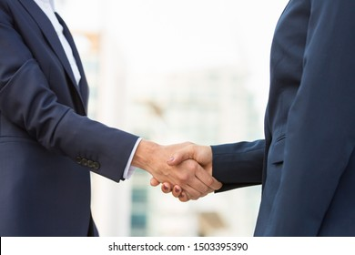 Female business partners meeting outside. Business women in office suits standing and shaking hands. Collaboration concept