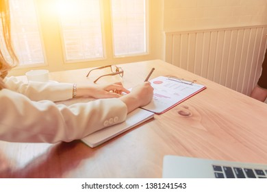 Female business women are checking the property accounts and annual sales to summarize the results. Business women are summarizing sales to close the annual budget alone near the window in the morning.