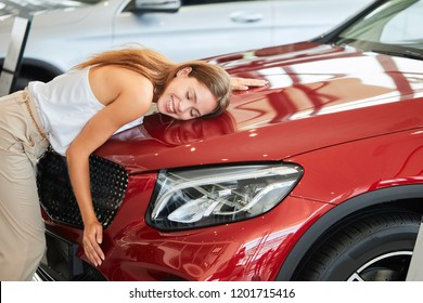 Female businessman loving her new car, hugging and pressing herself to car hood at car show room.