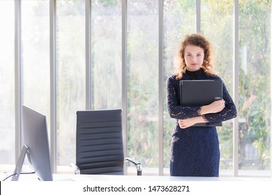 A female businesswoman, wavy hair, is standing, hugging work files with confident facial expressions and eyes that look determined at her desk with computers placed in the morning.