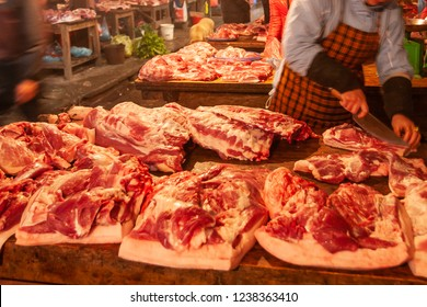 Female butcher cutting the meat in butchery counter, local butcher's shop at Sapa Market, Sa Pa. This market is a tourist attraction in Vietnam. Shallow dept of field. Warm tone. Food culture.