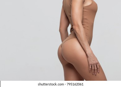 Female butt, white background. Beautiful female butt in a Thong.