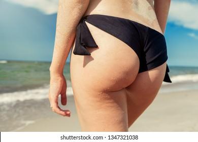 female buttocks with cellulite in swimwear on sea background closeup