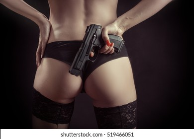 female buttocks in panties with gun on black background