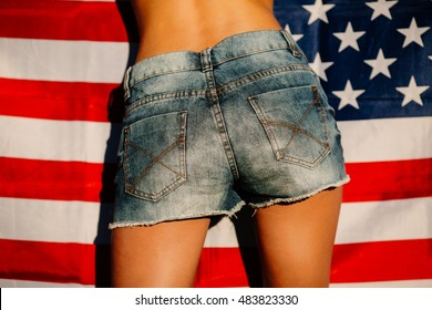 Female buttocks in short denim shorts on a background of the American flag.