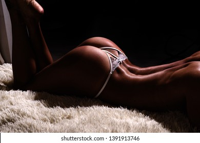 Female buttocks smooth skin. Sexy buttocks white lingerie. Attractive female ass. Erotic massage. Perfect buttocks. Waiting for you. Escort service. Desire concept. Sexy woman relaxing on fluffy bed.