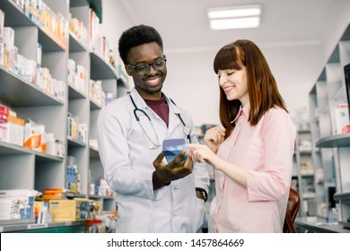 Female buyer consults with man pharmacist in drugstore