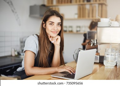 Female cafe owner using laptop computer waiting for first client in the morning looking at camera smiling.