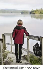 "a female camper admires a beautiful landscape of ""lac des cypres"" lake at sunrise, canada, quebec, mont-tremblant national park"