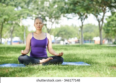 Female cancer survivor practicing yoga in the park