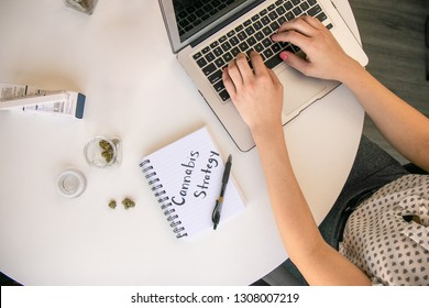 Female Cannabis Entrepreneur working on Strategy for Marijuana Business on White Table Work Space