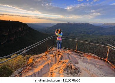 A female captures a stunning sunrise over mountainous landscape with her mobile phone