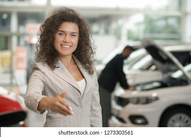 Female car dealer smiling and holding hand for shaking. Happy manager making deal in car showroom. Beautiful with curly hair looking at camera, posing. Client of car center observing vehicle behind.