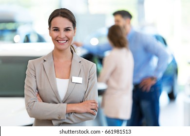 Female car dealer standing in showroom
