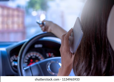 Female in car using remote control to open the automatic gate while phoning and leaving from home, security system and save time concept.