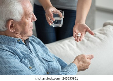 Female caregiver giving the medicine to her older male patient