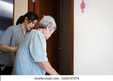 Female caregiver is helping support elderly woman walk into the restroom carefully,asian senior with bladder control problem need to use the toilet,old people suffer from Stress Urinary Incontinence