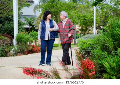 Female caregiver and an old woman are walking in a green park together. They look at each other and smile.