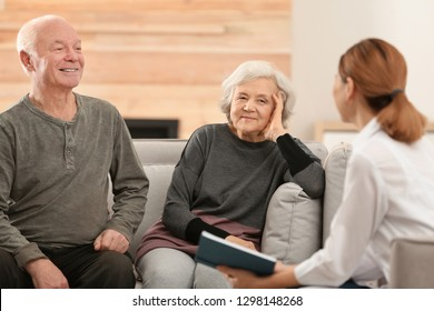 Female caregiver reading book to elderly spouses in living room