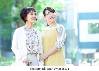 Female caregiver taking a walk with a senior woman