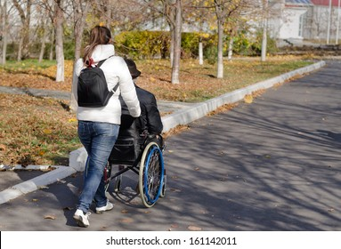 Female carer taking a disabled man in a wheelchair for a walk along the street as they walk away from the camera