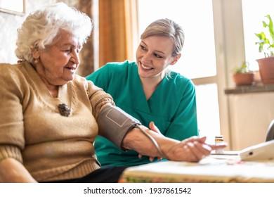 Female caretaker measuring senior woman's blood pressure at home
