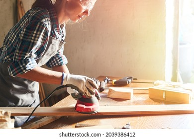 Female carpenter grinding wood with sandpaper in carpentry or diy workshop. Electric sander working in carpentry. Girl polishes wooden board with electric sander.