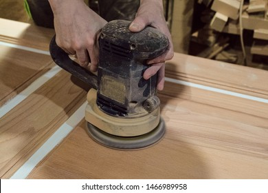 Female carpenter polishes the wooden door surface with electric grinding machine. Professional craftswoman with woodworking carpenter hand tool in working carpentry workshop.