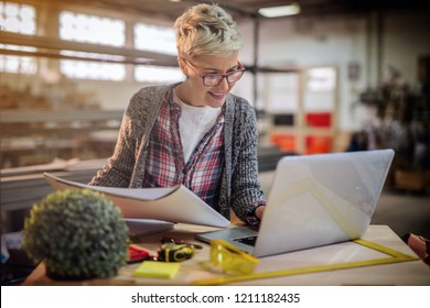 Female carpenter using laptop and in other hand holding drafts while standing in workshop.