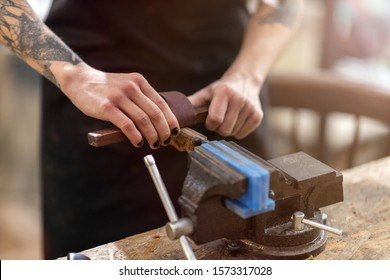 Female carpenter working on a vice grip