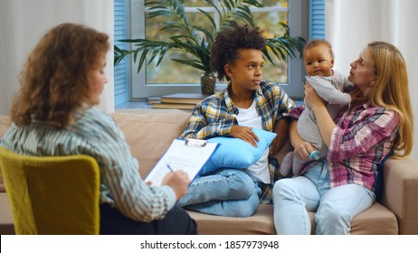 Female case worker visiting woman with adopted children. Back view of woman social carer talking to caucasian foster mother and mixed-race boy and baby in living room