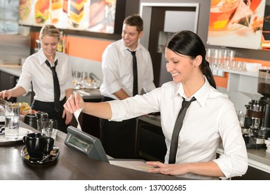 Female cashier giving receipt colleagues working in cafe