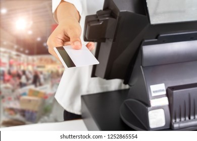 Female cashier hand holding credit card near monitor in supermarket shop.
